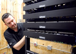 Siebern Visser, a member of the information technology department at Park Place of Elmhurst in suburban Chicago, tends to some of the behind-the-scenes equipment his department oversees. Technical dem