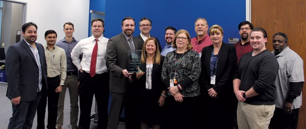 The Lexington Health Network team holding their Gold McKnight's Excellence in Technology Award in November at their office in Lombard, IL.