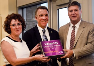 DAIL's Monica Caserta Hutt and Secretary of Aging Services Al Gobeille presented the SCAN Foundation's Pacesetter Prize to Gov. Phil Scott (R), center, in September.