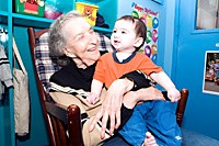 A resident at Isabella Geriatric Center interacts with a youngster from the childcare center.