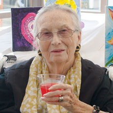 Resident Martha Cooner enjoys a bright drink and bright art.