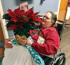 Woof Boom Radio employee Kevin Swain presents an Indiana nursing home resident with a poinsettia.